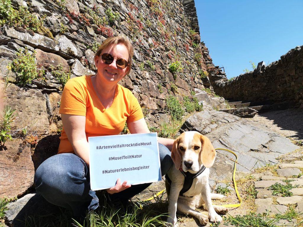 Christiane Beyer hält ein Schild mit #Artenvielfalt rockt die Mosel